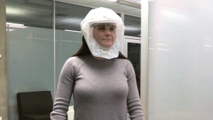 A woman in a face shield with a gray long sleeve shirt.
