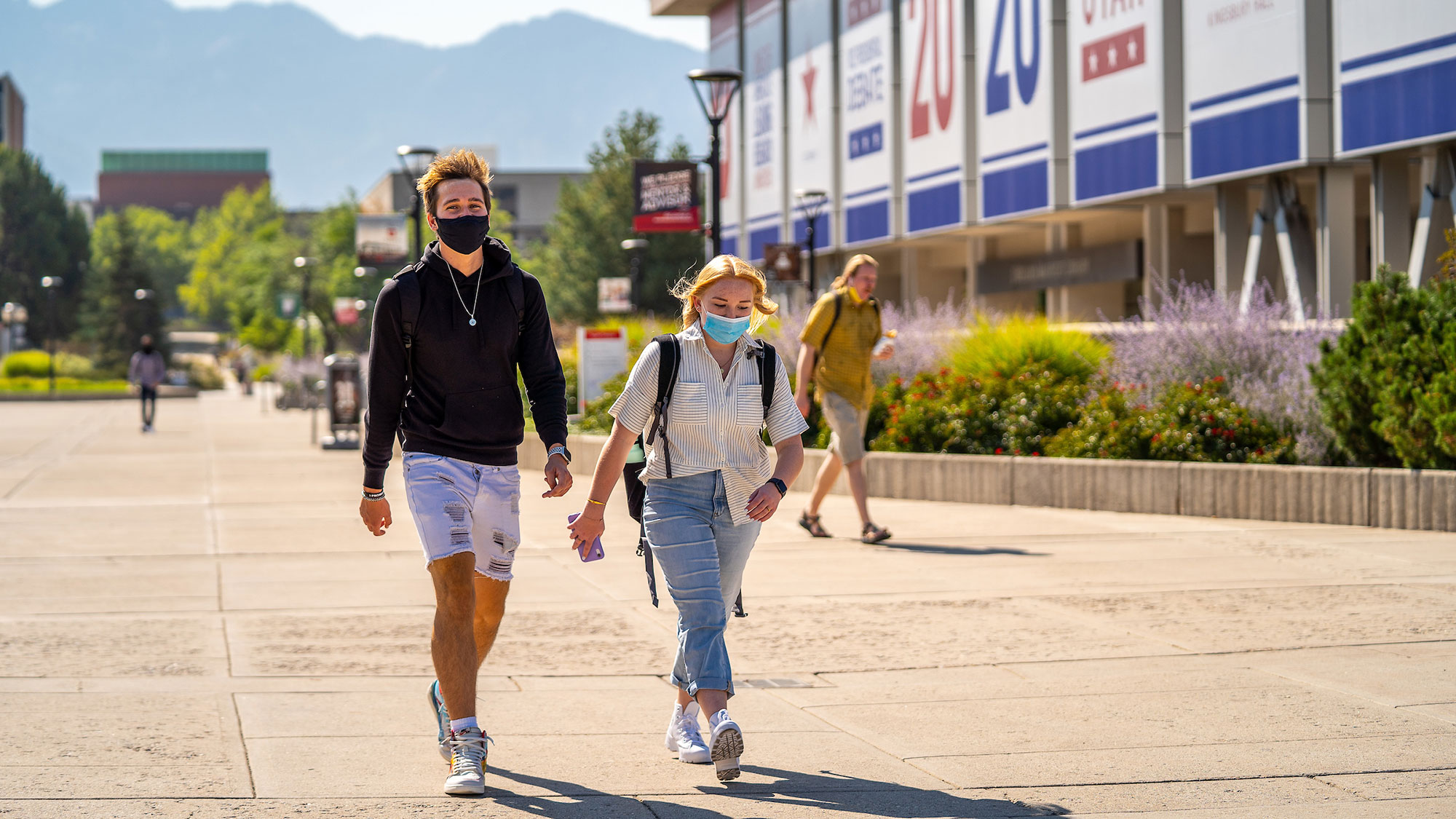 Two students walk on the University of Utah campus, both wearing masks.