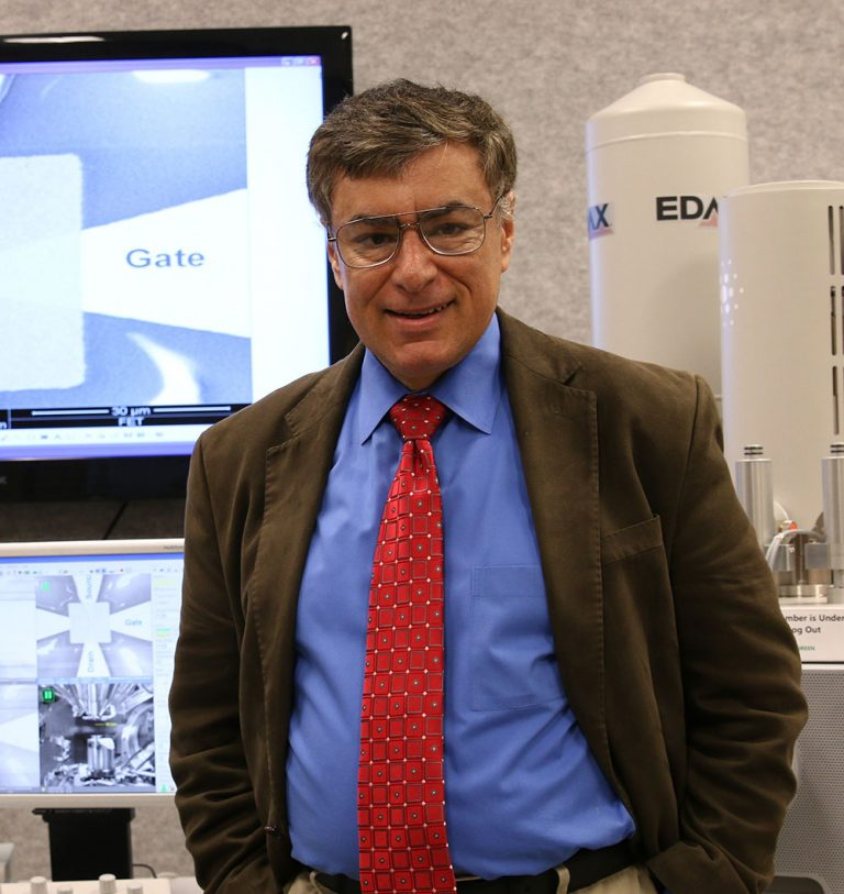A headshot of an engineer standing in front of technological equipment, in a brown jacket, red tie, blue shirt, wearing glasses.