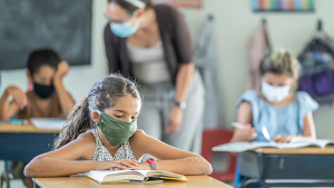 A child with a mask is in a classroom where everyone is wearing mask.