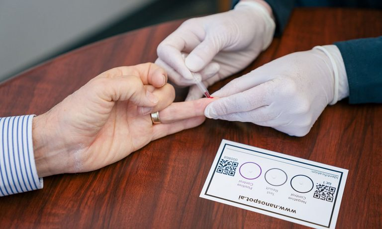 A close up of two people's hands. One person is wearing white rubber gloves pricking an ungloved finger. The testing card is on the table.