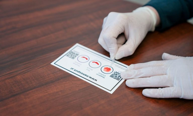 A white index-sized card with the nanospot website on the top. The center has three open circles that you smear blood on. The sides have a QRT code.